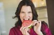 Portrait of a woman eating a slice of watermelon