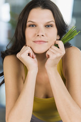 Portrait of a woman holding chives