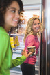 Woman giving a food can to her friend from a refrigerator