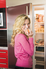 Portrait of a woman standing in front a refrigerator and eating an apricot