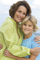 Woman smiling with her grandson on the beach