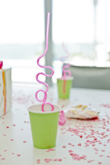 Disposable glasses with drinking straws and a birthday present on a table