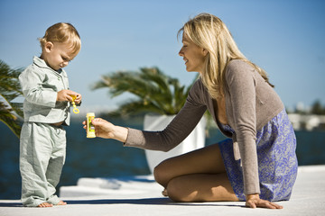 Woman holding a soap bubble bottle in front of her son