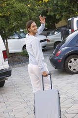 Man pulling luggage and waving hand