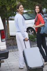 Couple holding luggage and smiling