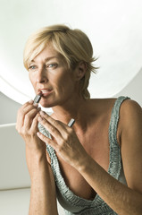 Close-up of a woman applying lipstick on her lips