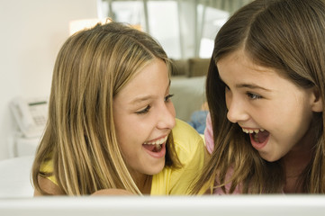 Close-up of two girls smiling at each other with a surprise
