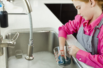 Girl washing a measuring jug at a sink