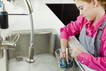 Girl washing a measuring jug at a sink