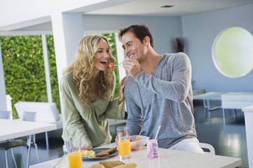 Man feeding fruit salad to his wife