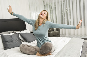 Woman stretching in bed and smiling