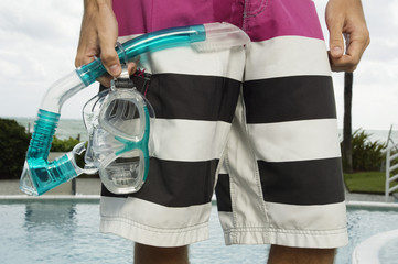 Mid section view of a man holding a scuba mask at the poolside