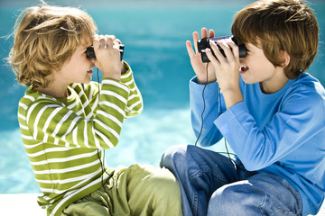 Two boys looking at each other through binoculars at the poolside