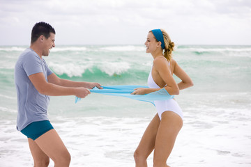 Man pulling sarong of a woman on the beach