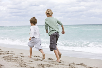 Rear view of two boys running on the beach