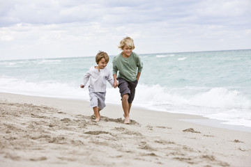 Two boys running on the beach