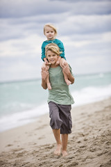 Boy carrying his sister on shoulders on the beach