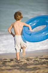 Boy carrying an inflatable ring on the beach