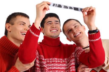 Three friends look at  film