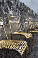 Old metal chairs along a stone wall