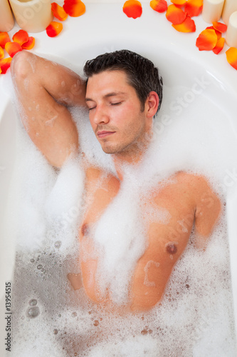 attractive man relaxing in foamy bath