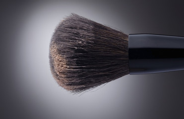 Stylish makeup brush with face powder on dark background