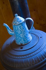 Antique coffee pot on pot belly wood stove..