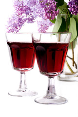 Syringa and glass of red wine on white background
