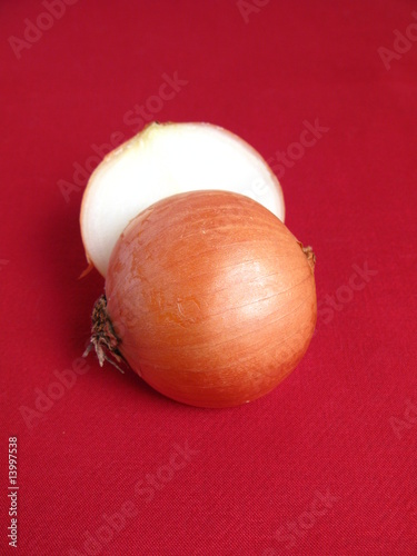 Onion cut in half, on red background