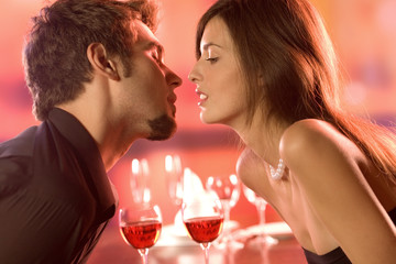 Young couple kissing in restaurant, celebrating or on date