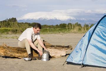 Mann neben Zelt vor Berg