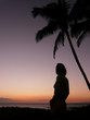 Silhouetted girl under a palm tree