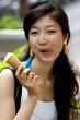 Portrait einer jungen asiatischen Frau beim Eis essen.