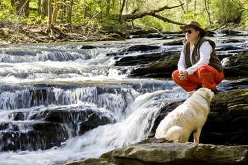 Man Looking Out Over River with Dog