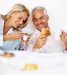 Elderly couple having breakfast on the bed