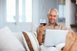 Mature man using a laptop while celebrating with wine