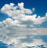 White clouds and blue sky mirrored in water poster