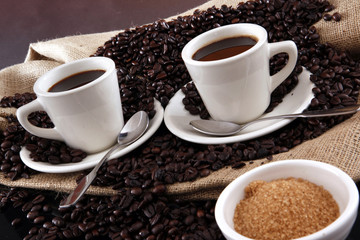 Cups of fresh brewed coffee and coffee grains from a sisal sack