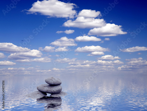 stones in water on a background bright blue sky