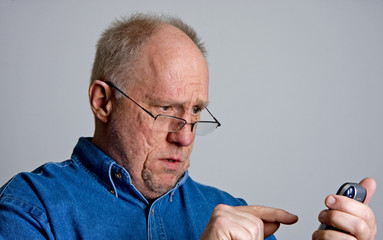 Older Bald Guy Trying to Dial Phone