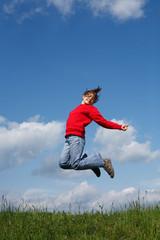 Girl jumping, running against blue sky
