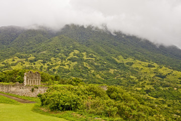 Lush Green Mountain and Ruins in Clouds