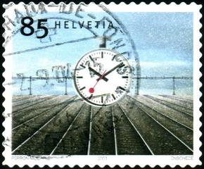 Helvetia. Rails et horloge. timbre postal oblitéré.