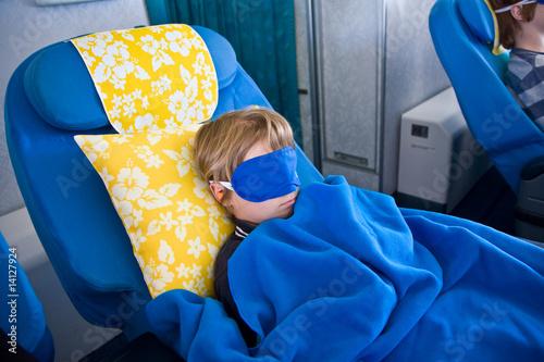 Passagier, Kind  in der Business Class schläft mit Schlafbrille