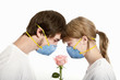 Young couple in blue masks look over rose