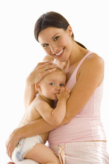 Young pregnant mother embracing baby girl, smiling, portrait, cut out