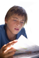 Teenage boy reading, close-up, cut out