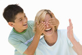 Boy covering mother's eyes, smiling, cut out