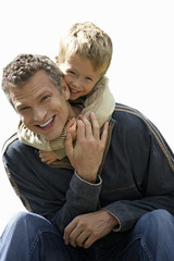 Boy embracing father, smiling, front view, portrait, cut out