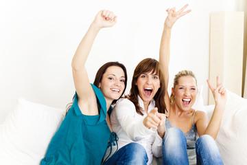 Freundinnen auf der Couch jubeln